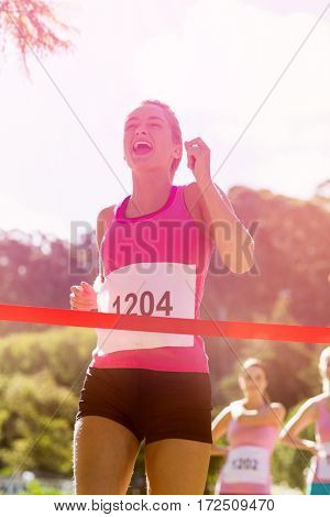 Cheerful winner female athlete crossing finish line in park