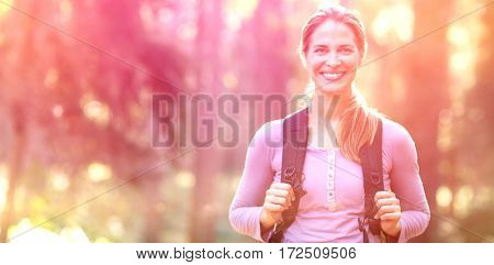 Portrait of smiling woman standing in forest carrying backpack