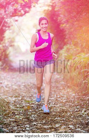 Portrait of happy woman jogging in field
