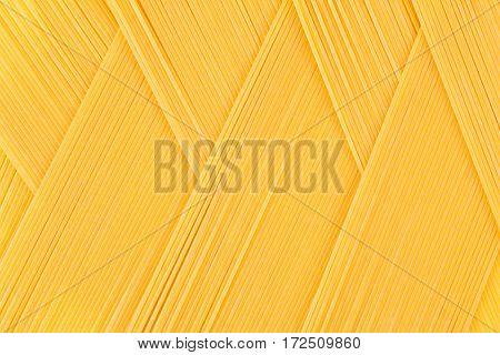 Italian long yellow spaghetti top view as zigzag abstract pattern background.