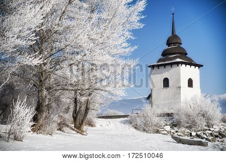 Frost on trees and tower of church. Blue sky