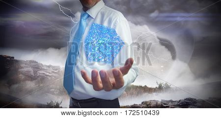 Businessman holding hand out against stormy sky with tornado over landscape
