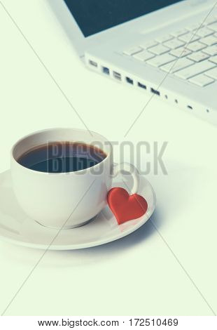 Laptop or notebook with cup of coffee and heart on table