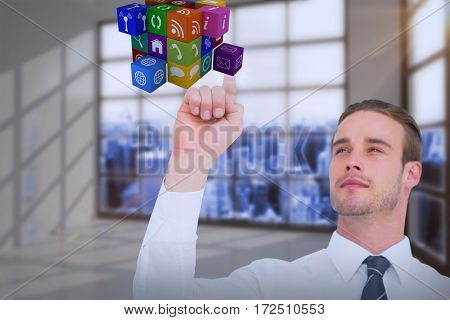 Cheerful businessman pointing cube with his finger against room with a lot of windows