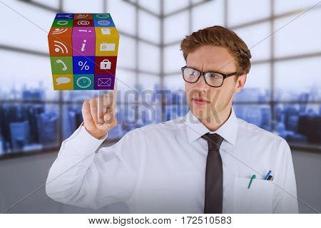 Geeky businessman smiling and pointing cube against room covered with windows