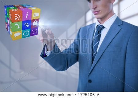 Midsection of elegant businessman pointing cube against white room with a lot of windows