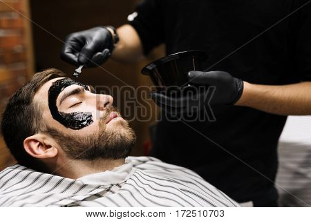 Barber applying purifying mask on his client face