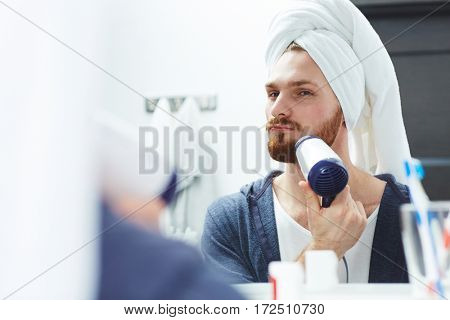 Young man drying his beard with blow-dryer