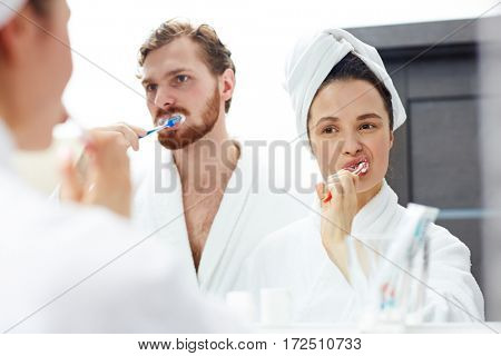 Young couple in white bathrobes brushing teeth in front of mirror