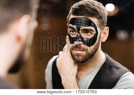 Man with luxurious peel-off mask on his face