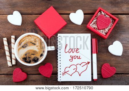 Valentines day background concept. Gift box with Valentine heart, cup of coffee with sweets open notebook with words Love you and pen on the wooden background. Writing romantic letters. Top view