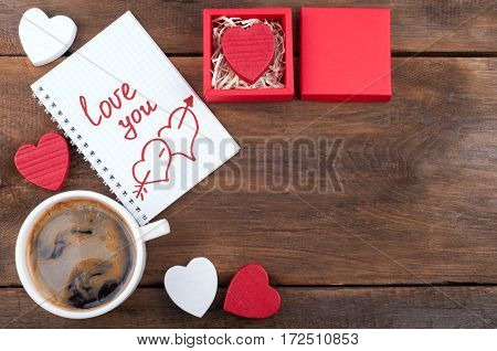 Valentines day background with copy space. Coffee cup, gift box with Valentine heart, open notebook with the written word Love you on old wooden background. Top view
