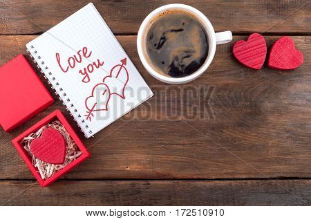 Valentines day background. Gift box with Valentine heart, cup of coffee, open notebook with the written word Love you on old wooden background. Top view