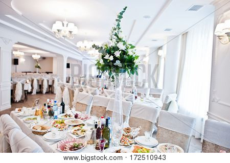 Bouguet Of Flowers On Vase At Guest Table On Wedding Hall.