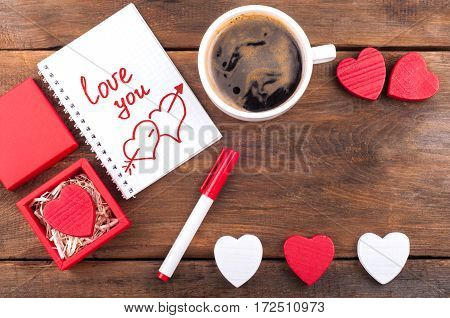Romantic I love you note on notepad, coffee cup and decorative hearts on old wooden background. Romantic present. Valentines day background. Top view