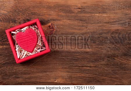 Gift box for Valentines Day. Valentine background. Valentine card with red heart in box on grunge wooden background. Top view