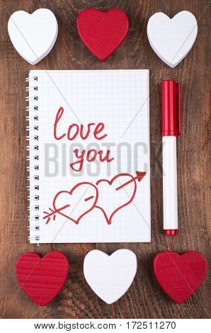 Valentines day background concept. Valentine heart and open notebook with the written word Love you on old wooden background. Top view
