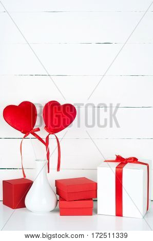 Valentines Day background. Gift boxes and hearts on wooden background. Copyspace