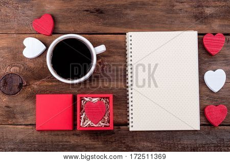 Valentines day background. Cup of coffee gift box with Valentine heart open blank notebook and wooden hearts on old background. Writing romantic letters. Top view