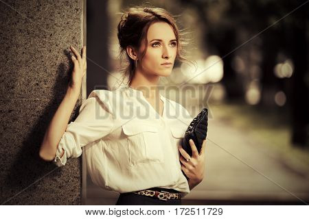 Young business woman standing at office building. Stylish fashion model in white blouse outdoor