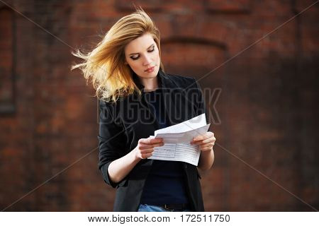 Young business woman reading a tax letter on city street. Stylish fashion model outdoor