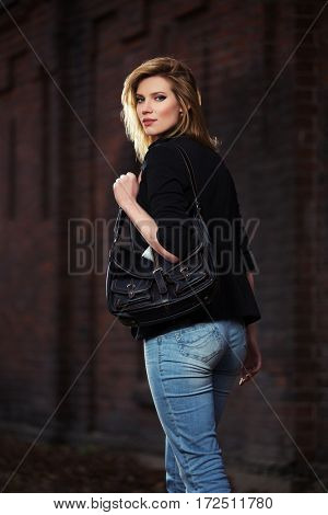 Young blond business woman with handbag walking on city street. Stylish fashion model outdoor