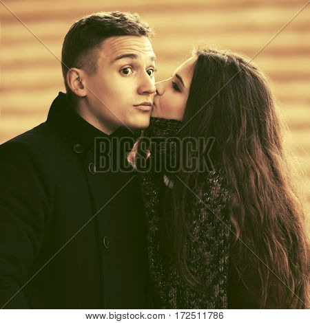 Happy young couple in love kissing on city street. Stylish fashion model outdoor