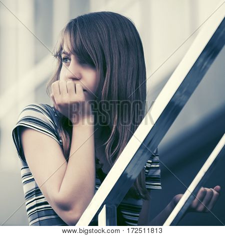 Sad teen girl on steps against a school building. Stylish fashion model outdoor