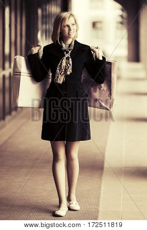 Happy young woman with shopping bags. Fashion model in black coat outdoor