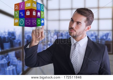 Thoughtful businessman pointing cube with his finger against room with a lot of windows