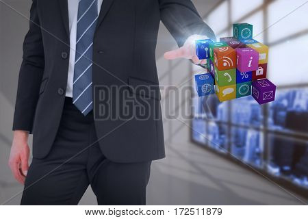 Mid section businessman pointing cube with his finger against white room with a lot of windows