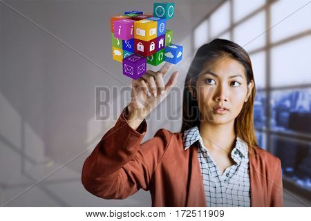 Businesswoman pointing cube against white room with a lot of windows