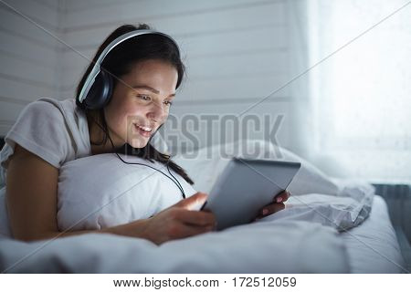 Girl with headphones looking in touchpad