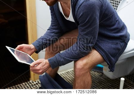 Mobile man sitting in lavatory with touchpad