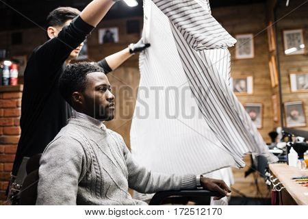 Owner of barbershop serving his client