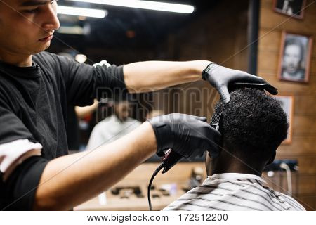 Young man cutting hair of his client with clipper