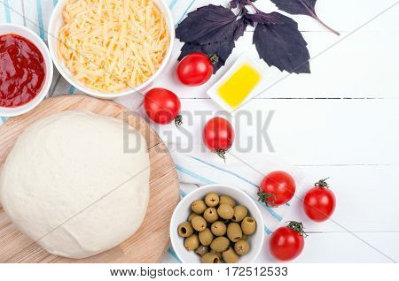 Pizza cooking background with dough vegetables and spices. Ingredients for cooking pizza - tomatoes, olive oil, dough, basil, ketchup and olive.Top view
