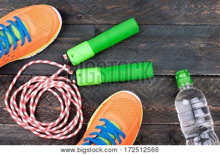 Sport shoes skipping rope and bottle of water on the old wooden background. Sports equipment. Sport diet and healthy life concept. Top view