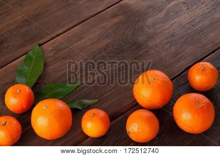 Tangerines with leaves on wooden background. Fresh mandarin oranges fruit background