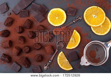 Chocolate truffles with orange and cinnamon. Candy chocolate citrus vintage dessert spoons on stone background. Process of cooking of homemade sweets. Top view