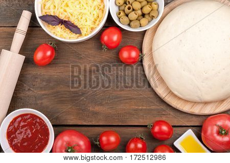 Ingredients for cooking pizza. Dough rolling pin tomatoes olive oil olives tomato sauce basil and cheese on a wooden table