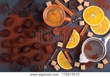 Handmade chocolate truffles with orange and cinnamon. Candy chocolate citrus cinnamon vintage dessert spoons and a cup of coffee on stone background. Process of cooking of homemade sweets. Top view