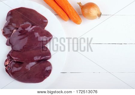 Liver and vegetables on a wooden background. Ingredients for liver or pate. Rustic style. Top view