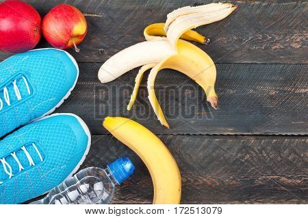 Sport and healthy life. Sport shoes apples bananas and bottle of water on a rustic wooden background. Sport equipment. Conceptual photo. Top view