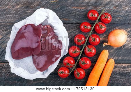 Raw liver and vegetables tomatoes carrots and onion on rustic wooden background. Ingredients for liver or pate. Top view