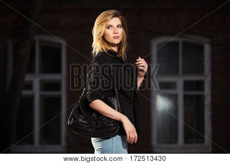 Young blond business woman with handbag walking in night on city street. Stylish fashion model outdoor