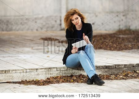 Young blond business woman using tablet computer on city street. Stylish fashion model outdoor