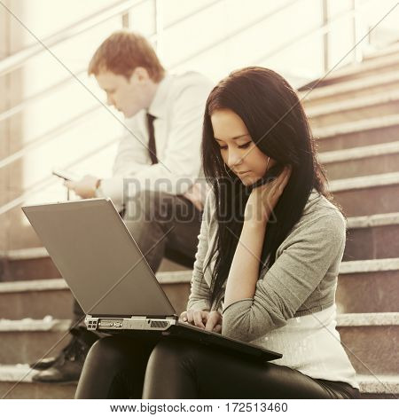Young business woman using laptop on the steps. Stylish fashion model outdoor