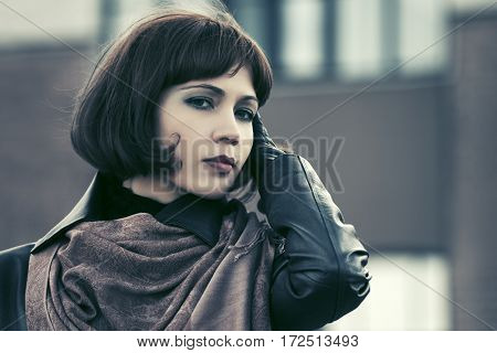 Beautiful woman in leather jacket walking on city street. Stylish fashion model outdoor