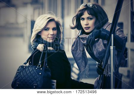 Two happy young women on city street. Stylish fashion model outdoor